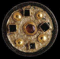 Round merovingian fibula in gold-plated bronze, pate de verre, that was discovered in a tomb.  c. 600.