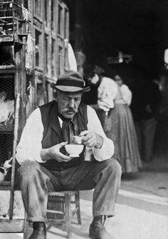 1910 - Homem sentado comendo, próximo a gaiolas com galinhas. Foto de Vincenzo Pastore. Acervo do Instituto Moreira Salles.