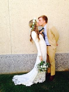 I love the lace on the dress and I love the floral hair crown. the way she's grabbing his tie is cute too.
