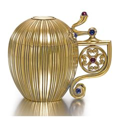 A Russian jewelled gold tankard, probably Alexander Treiden, possibly for Hahn, St Petersburg, circa 1895, reeded egg-form body, the hinged lit inset with a gold ruble of Catherine II dated 1779, the scroll handle enclosing a rosette and set with cabochon sapphires and garnets.