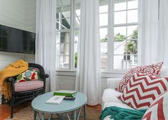 """Cozy little sunroom living area   House of Turquoise: Jane Coslick's Cottage on the Green   What was once quarters used for soldiers during the Spanish-American War transformed into a vacation rental on Tybee Island. Every room is enough to put a smile on your face. Favorite spaces are the bedroom with the matching turquoise Jenny Lind beds, and the breezy sleeping porch with the fab pink bed... Available for rent through Mermaid Cottages.""""   LFF Designs   www.facebook.com/LFFdesigns"""