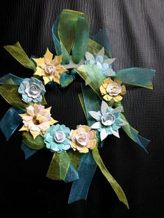 This is a lovely paper floral wreath made from a cardboard ring decorated with pastel blue and green chiffon ribbon and beautiful layered and shaped paper flowers in pastel blue,lemon and cream some with brad centres. It has a hanging loop but would make a nice candle decoration but please remove before lighting candle. It comes tissue wrapped in a handmade box and would make a lovely gift.