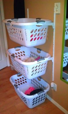 Use a shelving unit (you can get them from IKEA for cheap) to stack and store your assortment of laundry baskets. It doesn't use up any extra room as you're just taking advantage of unused vertical space. I'm just a little worried about that neon pink sock in the lights basket.