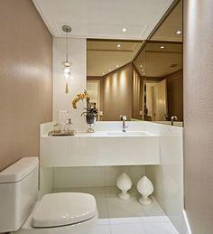 Bronze mirror, spotlights, white quartz counter and floor. Low profile toilet.