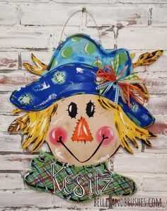 Scarecrow door hanger for Fall! I don't know that it will scare the crows away but it will certainly brighten up you Fall decor! Handpainted in my unique style. #scarecrow #doorhanger #falldecor #happyfall