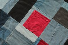 Interspersed with black and red squares, our #upcycleddenim #cribquilt makes a classic and unique coverlet for cribs or toddler beds. Blue Jeans Quilt Denim Baby Construction by HandiworkinGirls