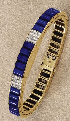 Cartier bracelet, the hinged central panel opening to reveal a rectangular dial with baton indicators, to an articulated bracelet, the links composed of a series of carved lapis lazuli batons highlighted at intervals with pairs of brilliant-cut diamond set links, length approximately 165mm, signed Cartier to dial.