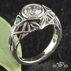 Custom platinum mounting with round brilliant cut diamond bezel set in hexagon. Bezel set trillion cut emerald side stones. Pierced geometric design on top and side face half way down shank.