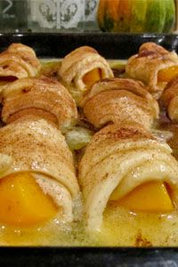"Martha's Peach Dumplings 4 lg, ripe peaches 2 pkg - crescent rolls cinnamon sugar  Syrup: 2 c - water 1 1/2 c - sugar 1/2 c - butter  Peel the peaches and cut each one into 4 pieces. Divide the rolls into triangles. Roll the peaches up and place into a 9"" x 13"" pan. Bring the syrup ingredients to a boil. Pour over the rolls. Sprinkle with cinnamon and sugar and bake at 350° for 30 minutes."