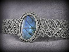 Vous recevrez ce bracelet gris clair en macramé, orné dun cabochon de labradorite dun beau bleu et de perles argentées.  La labradorite est une