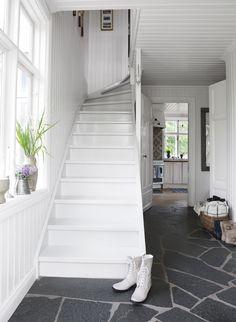 På golvet i hallen ligger jämtländskt Offerdalsskiffer. I bakgrunden köket med sitt blåvita kakel.