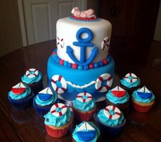 Two tier baby shower cake with anchor and ocean with baby on top and accompanying cupcakes