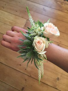 A stunning corsage with peach spray roses, white astilbe, eucalyptus and Eryngium.