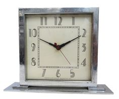 This American art deco clock was designed in 1930's by Gilbert Rohde (1886 - 1958) for the Herman Miller company. The clock features a stepped chrome base, chrome frame and black skyscraper hands