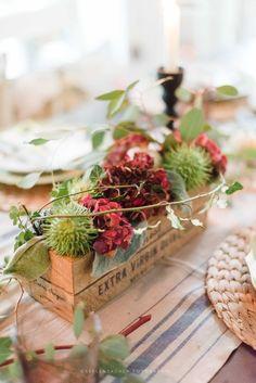 Herbstliche Tischdekoration mit Kastanien, Hortensien und etwas Efeu, arrangiert in einem Holzkistchen