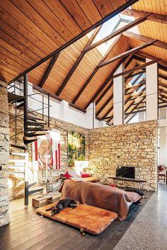 Polovina domu je otevřená do krovu, prosklenou částí střechy u hřebene je vidět obloha.
