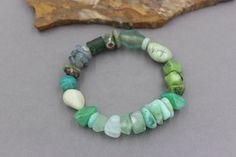 This mixed gemstone nugget bracelet is mainly green. It is easy to wear with just about anything and easily pairs with other bracelets for a great stack. Stones include Chrysoprase, Turquoise, Moonstone, Fluorite, Prehnite, Amazonite, Moss Agate, Aqua Terra Jasper, Bloodstone and Peruvian Blue Opal beads. There is also an ancient Roman glass bead and a handmade stoneware bead.  This bracelet measures 7 1/2 and easily rolls on and off to fit most wrists.  Find other bracelets here…