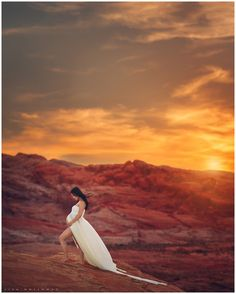 Beautiful pregnant woman poses for her maternity photo session on the red desert rocks outdoors near Las Vegas at sunset