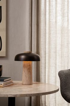 The conical base and the curved shade define the lamps perfectly balanced expression. Where the shade meets the base is a dimmer switch for adjusting the light intensity from 2200K to 2960K color temperatures. Perfect for a bedside table or used as a subdued light on a cabinet. Available with a Travertine base complemented by a Bronzed Brass shade. UL listed.
