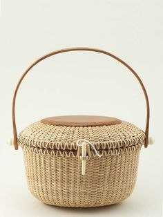 """Our Nantucket Oval Lidded Nantucket Basket, Cherry is a beautiful traditional lightship basket, using cherry wood for the base, lid, rim and handle.  The contrast in woods is stunning.   7 1/2"""" L x 5"""" W x 5"""" H  Imported"""