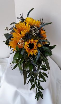 Sunflower wedding bouquet with blue veronica and eryngium, mixed greens in a teardrop shape and a touch of baby's breath.