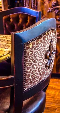 ~ What a fabulous chair design. Leather and wood...my two fav elements. I love the look of leopard print-back chairs showcasing a great fleur-de-lis design and surrounded by nailhead accents inside the frame. ~