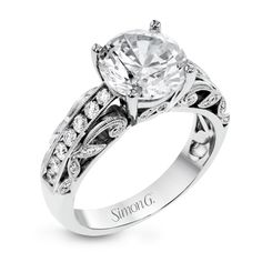 This 18k white gold engagement ring has a design taken from nature with leaves and filigree set with .43 ctw of white diamonds.