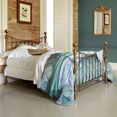 teal blues and orange/red brick set off by the white bedding. pretty with brass bed