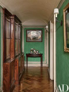 A hand-painted motif frames the green cloth walls of the corridor leading to the kitchen; an antique Gillows bookcase stands at left, and the circa-1800 English console is surmounted by a Neapolitan gouache   archdigest.com