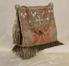 New handbag from 19th century French handmade silver lace and cross applique mounted on vintage tomato red and metallic silver Fortuny fabric. 19th c. French silver coil fringe and antique handmade silver tassel. Hidden magnetic closure and silk lining. Antique silver cord handle with threaded bobble. Wear with jeans or dress up for evening.