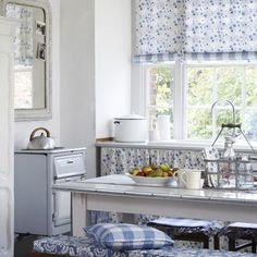 Clarke and Clarke - Genevieve Fabric Collection - White fabric and blinds with a tiny blue flower print, blue and white bench cushions, checked scatter cushion, large glass-topped wood table