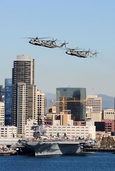 A formation of Navy and Marine Corps CH-53 Super Stallion helicopters flies past the USS Midway aircraft carrier museum at San Diego's historic Broadway Pier during the city's Centennial of Naval Aviation Open House and Parade of Flight.