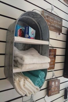Galvanized tub up-cycled into a hanging wall shelf cupboard towel rack. Great for a bathroom or laundry room.