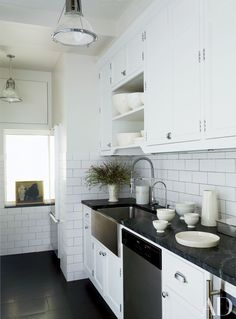 Subway tile by Nemo Tile Co. lines the kitchen of a classic prewar New York City apartment owned by designers Richard Lambertson and John Truex. The space also features a Bosch dishwasher, a Blanco sink, and vintage factory lights from R. T. Facts.