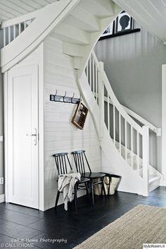 valkoiset portaat, musta lattia, komero portaiden alla