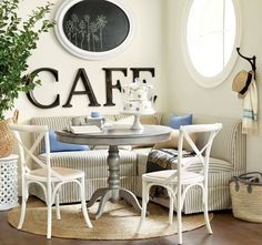 A striped banquette, painted gray pedestal table, and round natural fiber rug is a guaranteed win in our book.