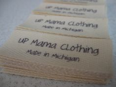Twill Fabric Labels, three-quarter-inch ribbon - cut and fraychecked - natural $22.00, via Etsy.  (This is what I want.  Top sew-in.)