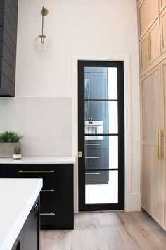 black glass pantry pocket door with steel transoms in modern kitchen #homekitchendesign