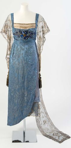 Blue figured silk evening dress with gold net sleeves and train embroidered in gold metal strip and decorated with blue gems and tassels, by Lucile (Lucy, Lady Duff Gordon), 1911, at the Fashion Museum Bath. Worn by Esme Giffard (née Wallace), daughter of Lucile, to celebrate the Coronation of King George V in 1911 and later altered for a Ball in 1919.