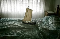 """""""Ara Solis"""" is a delightful photo series of model ships sailing across rumpled beds. The series was created in 2010 by Guatemalan photographer Luis González Palma."""