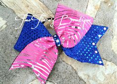 Pink Zebra Foil Chevron tick tocked with royal blue sequin Cheer Bow by Two Tiara's Bowtique on Etsy or Facebook group. Team discounts are always available.  Etsy listing at https://www.etsy.com/listing/187942396/pink-zebra-foil-and-royal-blue-sequin