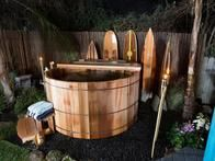 This red cedar hot tub, surrounded by decorative surfboards and tiki torches, makes every day feel like a day at the beach.
