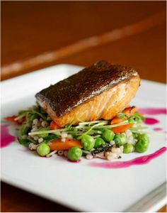 A hearty salmon sitting atop a green pea salad at Viceroy Snowmass.