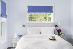 Silver gray and blue bedroom features a silver gray headboard on bed dressed in soft white bedding, placed under a window dressed in a denim blue roman shade, flanked by white mid century nightstands by West Elm illuminated by Jonathan Adler Havana Wall Sconces.