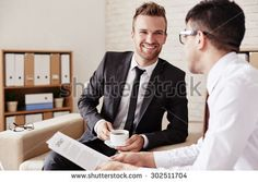 Confident businessmen interacting in office at meeting