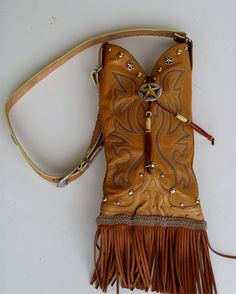 This prairie tan vintage leather NOCONA cowboy boot purse is!  Her name is Shy Ann and she sports a raised Texas star concho and buckskin leather fringe on the bottom.  Her closing strap is leather lacing with silver beaded rings and white and maroon bone beads.  Her carrying strap is an adjustable vintage western belt.  She will be the topic of conversation when you take her out with you.
