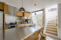 キッチン脇にも開口がつくられて外の景色を眺めることができる。外に植えられたグリーンも西間木さんと打ち合わせて決めたもの。