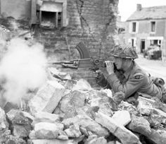A British soldier from 6th Battalion Durham Light Infantry fires his Bren gun from a ruined house near Bayeux, 1944.