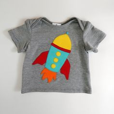 Glammic's Grey Baby Tee with Rocketship Applique, perfect for your little future astronaut! $35.