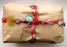 Good old recycled paper is better than nothing! And I like the addition of buttons used to make it interesting. Reused ribbon/string and raiding that store of spare buttons that every respectable woman has would be perfect for this sustainable wrapping!